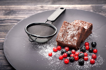 Chocolate brownies with berries and icing sugar