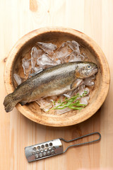Raw trout fish with ice in wooden bowl. top view