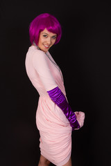 Young and beautiful woman in purple wig and dress