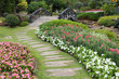 landscape of floral gardening with pathway and bridge in garden - 81065044