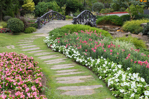 Foto op Plexiglas Tuin landscape of floral gardening with pathway and bridge in garden