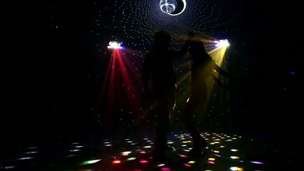 Girl and guy dancing in glow of LED spotlights. Slow motion