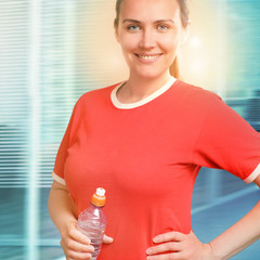 Portrait of young smiling woman holding water bottle at office