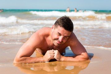 Smiling man lying on the beach on sea background