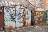 Two old rusted locked garages with grungy graffiti
