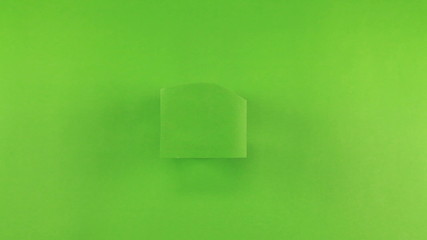 Hand of female put a white photo paper on green screen
