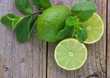 Juicy ripe limes and mint on wooden table - 81072269