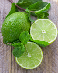 Juicy ripe limes and mint on wooden table