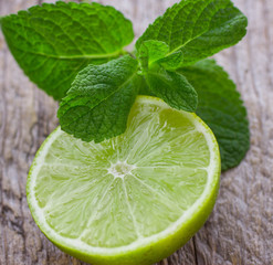 Juicy ripe lime and mint on wooden table