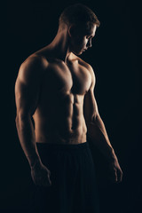Close up of sports man's muscular isolated on black background