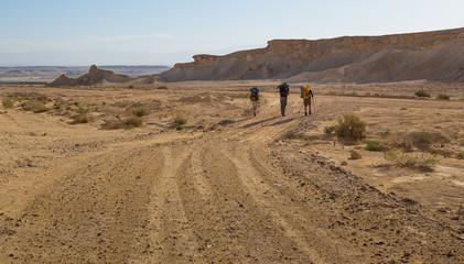 Backpackers walking desert road.