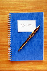 'To Do' List Book with Gold Coloured Pen on Oak Desk