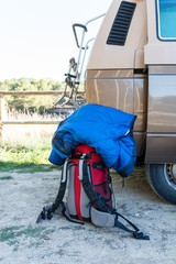red backpack and sleeping bag near a retro caravan