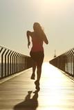 Fototapeta Runner silhouette running fast at sunset