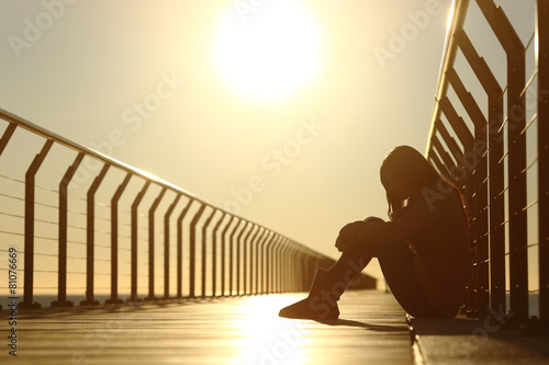 Leinwanddruck Bild Sad teenager girl depressed sitting in a bridge at sunset