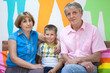Mature parents sitting with young son in bright color rooom