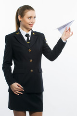 young girl pilot holding a paper airplane