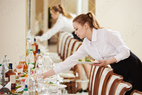 Leinwanddruck Bild waitress at catering work in a restaurant