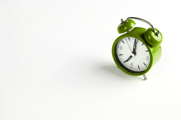 Seven o'clock. Green classic clock on white background.