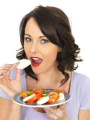 Young Woman Eating a Mozzarella Cheese and Tomato Salad