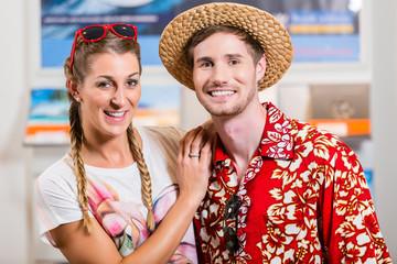 Paar im Reisebüro bucht Reise