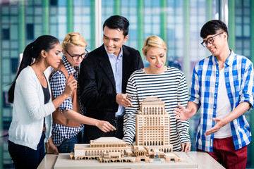 Team of architects presenting model building
