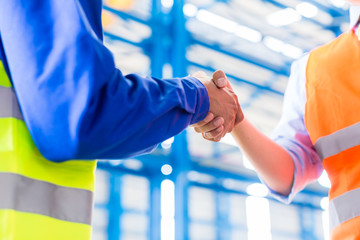 Worker and engineer handshake in factory