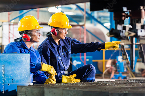 Leinwanddruck Bild Worker in factory at industrial metal cutting machine