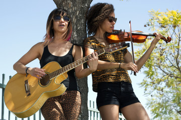 Two young women playing a guitar and violin next to tree