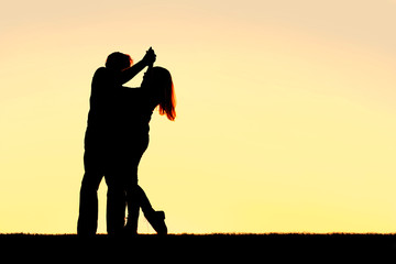 Silhouette of Happy Young Couple Dancing at Sunset
