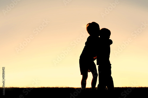 Silhouette of Two Young Children Hugging at Sunset - 81086412