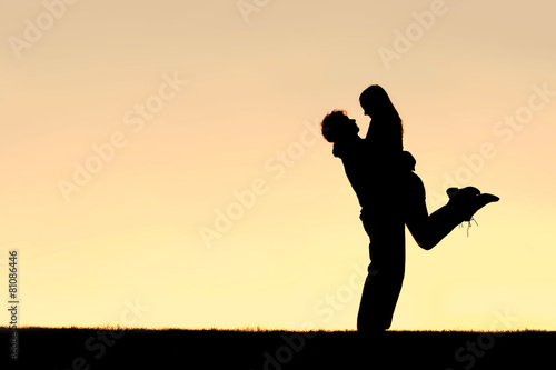 Silhouette of Happy Young Couple Hugging Outside at Sunset - 81086446