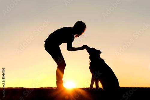 Leinwandbild Motiv Woman Feeding Pet Dog Treats Silhouette