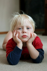 Adorable Young Child Laying on Living Room Floor