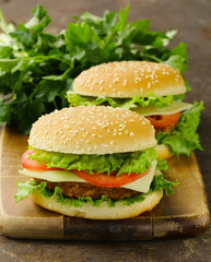 traditional cheeseburger with green lettuce and tomatoes