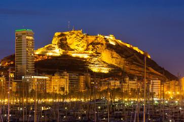 port  against Castle in night. Alicante, Spain