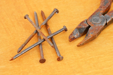 Rusty nail and wire cutter on wooden background, close up