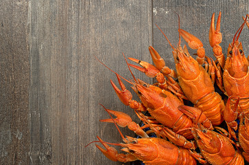 Plate of red crayfishes on old wooden table