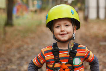 portrait brave little boy having fun at adventure park