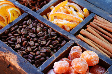 Coffee beans, dried fruits and spices in wooden crate