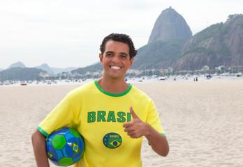 Brasilianischer Fan mit Ball vor dem Zuckerhut zeigt Daumen