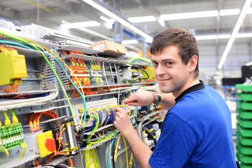 junger Arbeiter montiert Schaltschrank in einem Werk