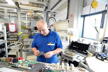 älterer Arbeiter montiert Bauteile in einer Chipfabrik