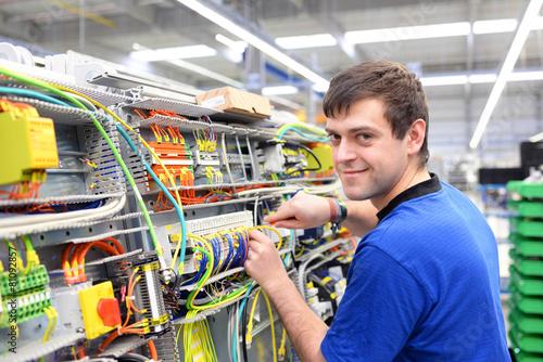 Leinwanddruck Bild junger Arbeiter montiert Schaltschrank in einem Werk