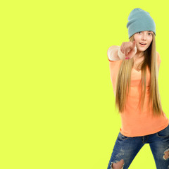 Beautiful joyful girl hipster pointing at you over acid yellow-g