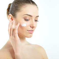Beautiful young woman applying cream on her face. Girl with perf