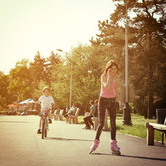 Teen girl on roller skates smiling and little boy bike on bicycl