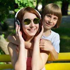 Boy and teen girl have fun outdoor in summer park. Happy childre