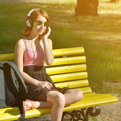 Young cheerful teen girl relax and listen to music outddor.