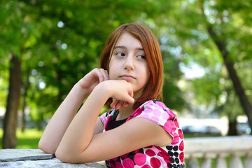 Young girl alone in park, face close up.